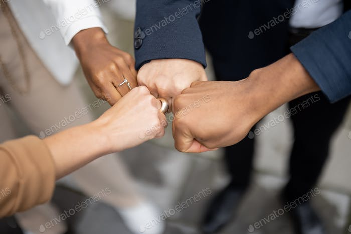 Cropped image of team bumping fists each other
