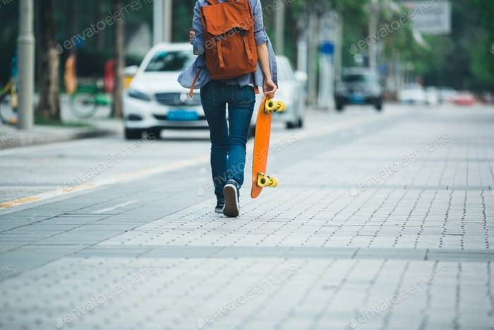 Skateboarder with skateboard on city