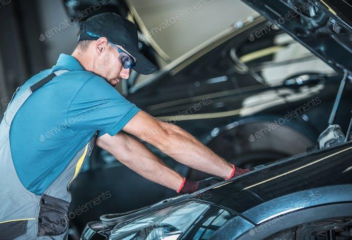 Worker Repairing Car