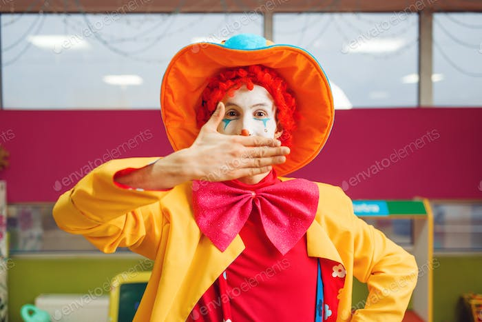 Funny clown shows tricks with facial expressions