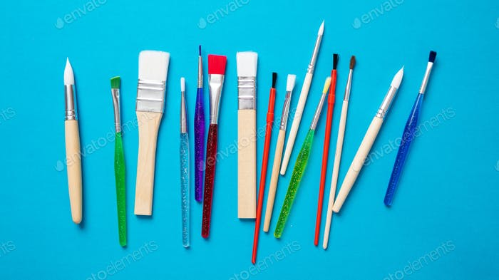 Paint brushes new clean isolated against blue background.