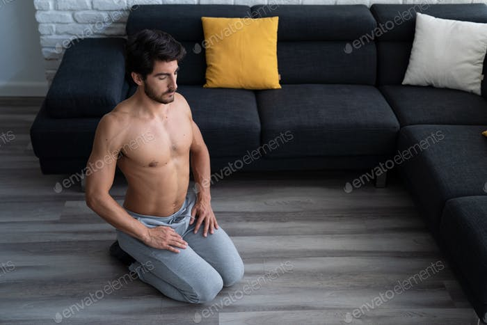 Young Fit White Fit Man Meditating At Home Alone