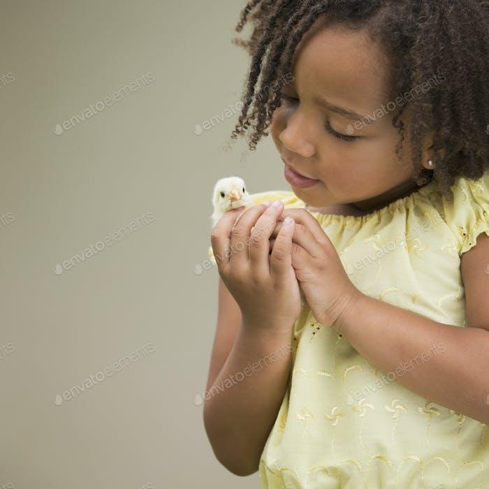 Ein Mädchen, das ein Baby-Küken hält.