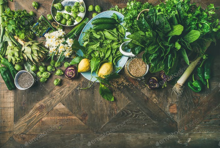 Spring healthy vegan food cooking ingredients over wooden background