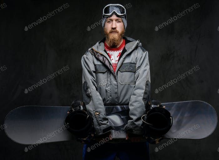 Brutal redhead snowboarder dressed in a snowboarding coat posing with snowboard at a studio