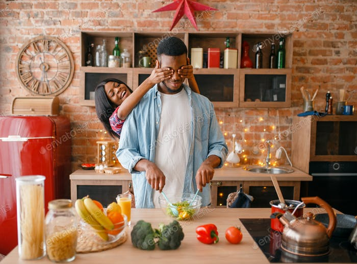 Black couple having fun while cooking on kitchen