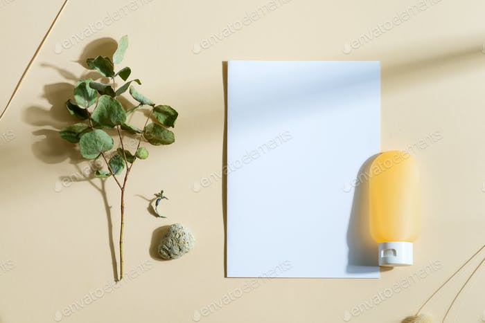 Mockup card with cosmetic lotion bottle and eucalyptus