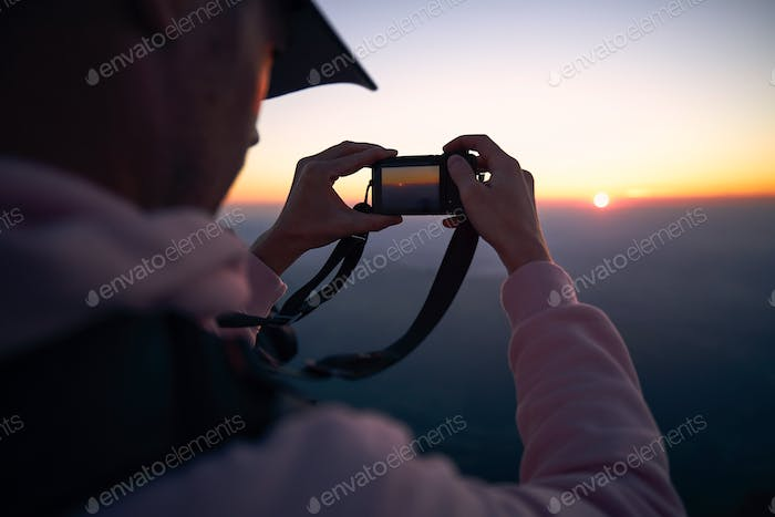 Man photographing sun under horizon