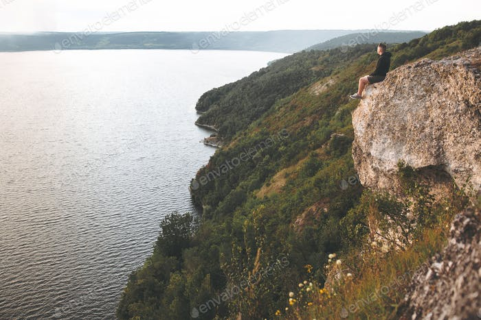 Hipster traveler sitting on top of rock mountain and enjoying amazing view on river