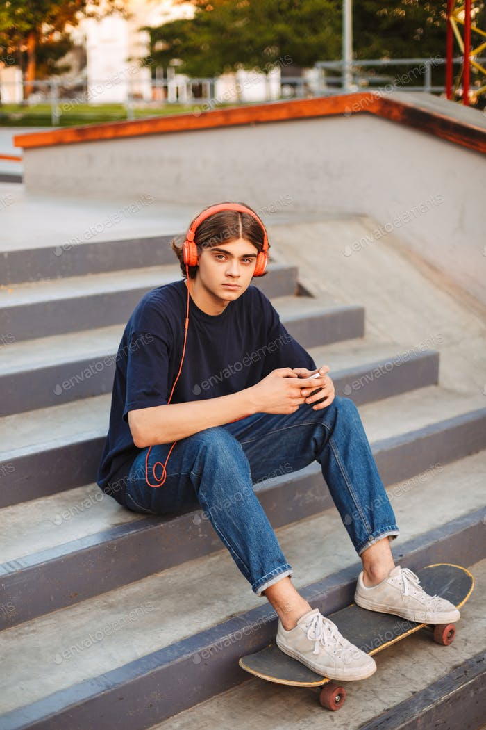 Young skater in orange headphones holding cellphone in hands tho