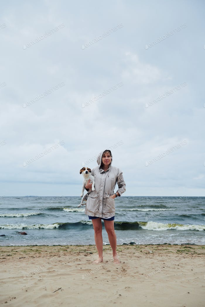 Young lady with dog near stormy sea