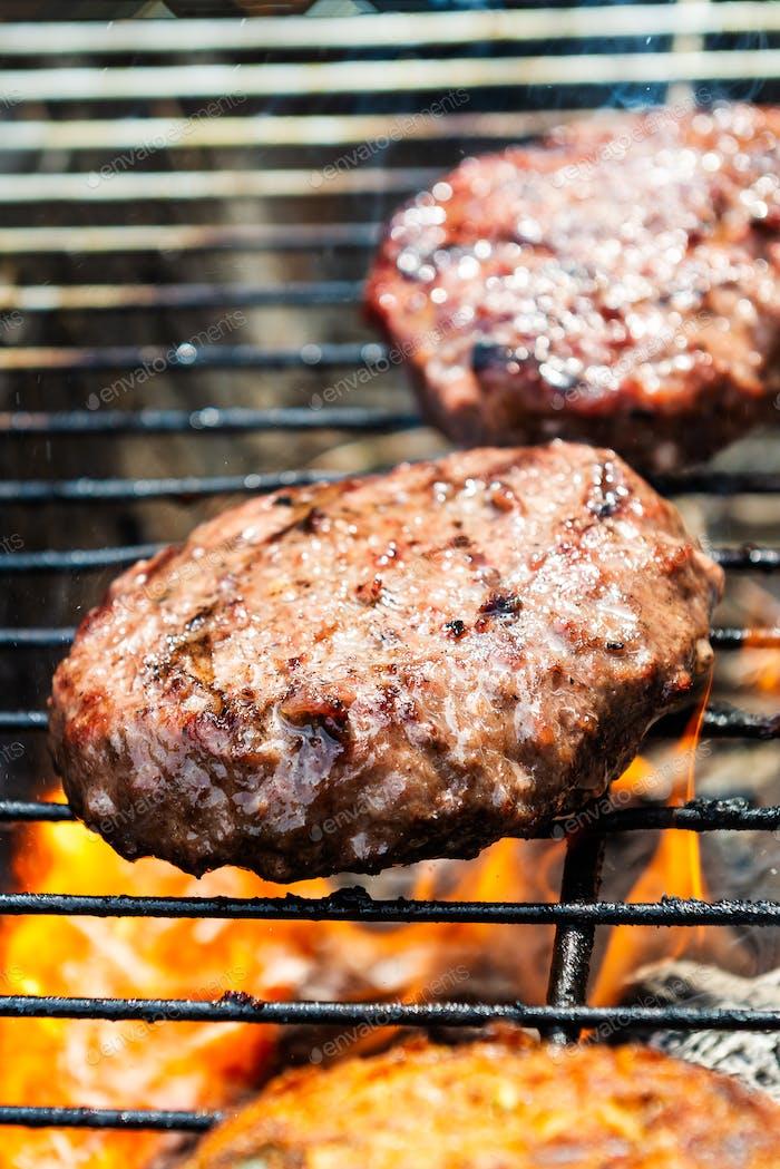 Burger kochen auf dem Grill mit offenen Flammen