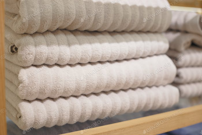Shelves with towels stacks in shop. Hygge or another scandinavian style