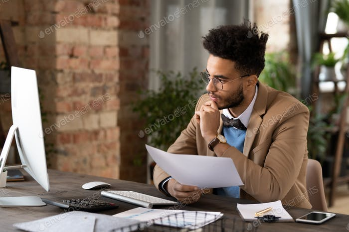 Busy African American manager comparing data on computer