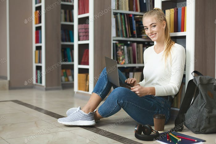 Young female graphic designer doing homework, sitting on floor