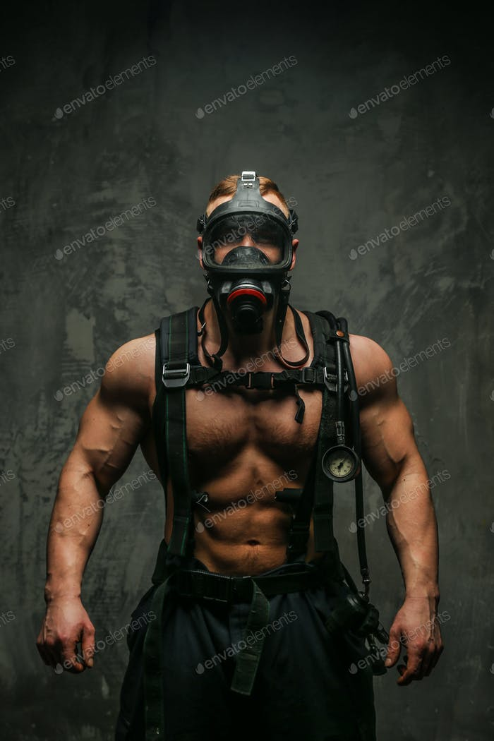 Muscular firefighter in oxygen mask