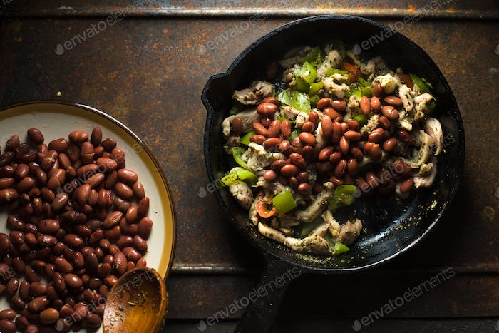 Beans are spread in a frying pan with pepper and chicken.