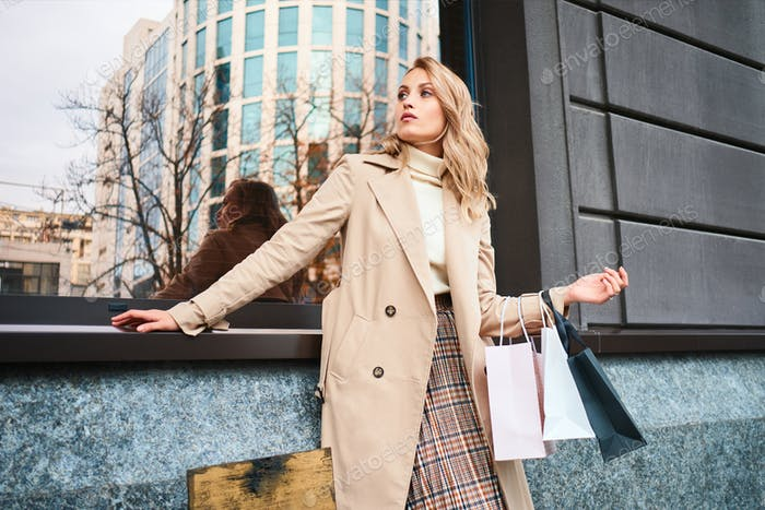 Stylish blond girl in trench coat with shopping bags confidently looking away on city street
