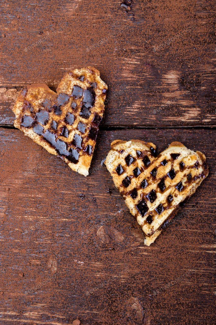 Two belgian heart shaped waffle with chocolate on wooden background. Flat lay. Copy space