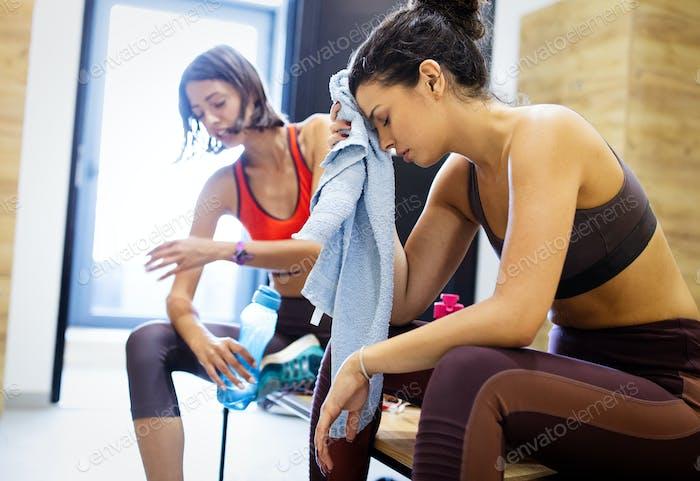 Müde Fitness Frau ruht nach dem morgendlichen Training im Fitnessstudio
