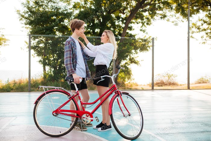 Young couple standing with bicycle and spending time together outdoors