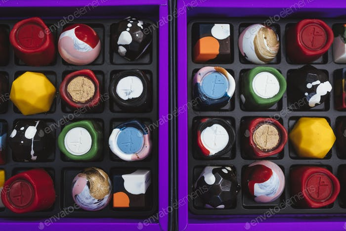 High angle close up of selection of bonbons in a purple and black box.