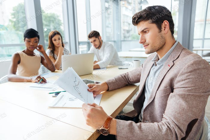 Businessman sitting and creating presentation with business team in office