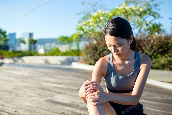 Frau hält schmerzhaften Knöchel im Park