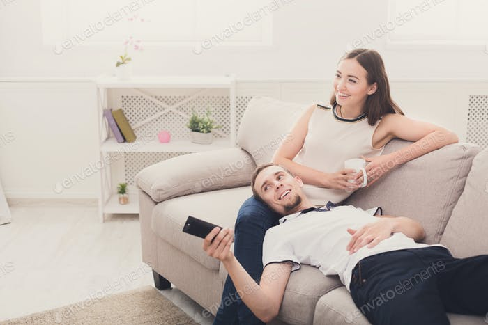 Smiling young couple watching TV at home