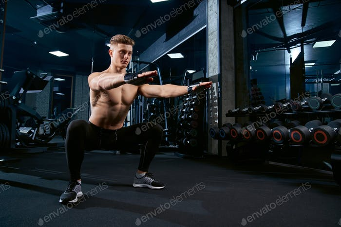 Sportsman doing squats in gym