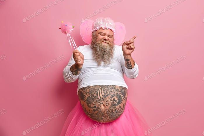 Joyful bearded adult man fairy dances carefree has fun on costume party holds magic wand closes eyes