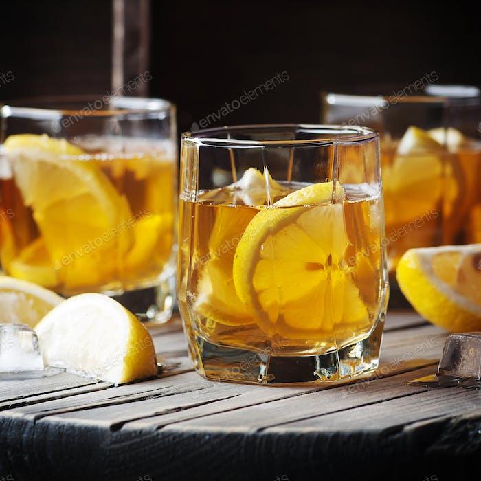Kalter Whisky mit Eis und Zitrone auf dem Vintage-Tisch