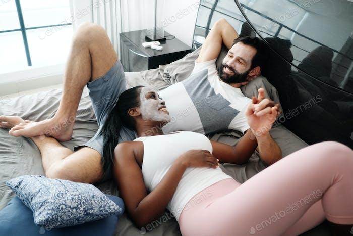 Glücklicher Mann und Frau mit Beauty-Maske Auf Bett