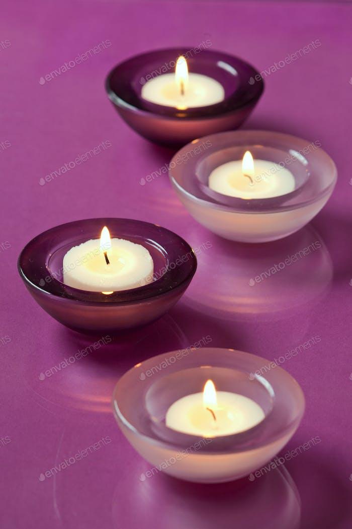 brennende Kerzen auf lila Hintergrund