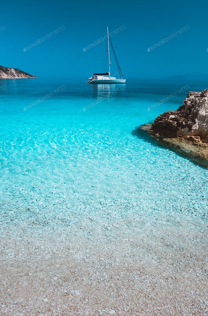 Lonely white sailing catamaran boat drift on calm sea surface. Pure azure clean blue lagoon with