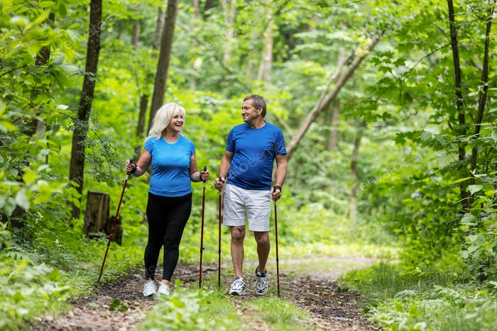 Elderly couple enjoying summer walk in the forest.