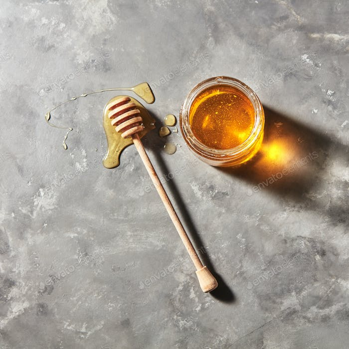 Natural sweet dessert - organic honey in a glass pot with dipper on a gray stone table. Top view
