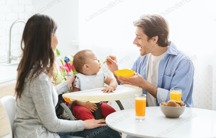 Millennial family having breakfast together at kitchen