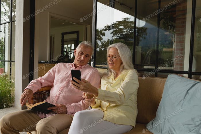 Active senior Caucasian couple using mobile phone and reading a book in the porch at home