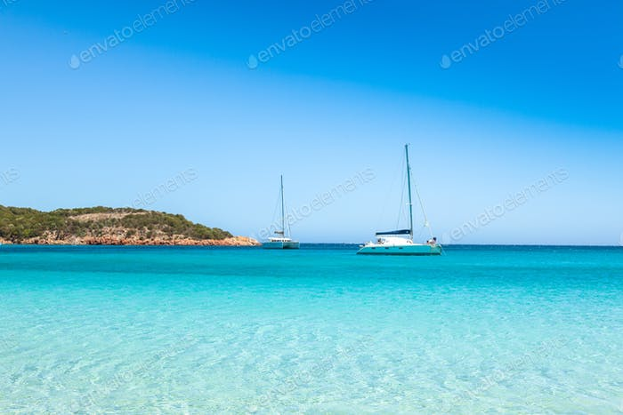 Boats mooring in the turquoise water of  Rondinara beach in Cors
