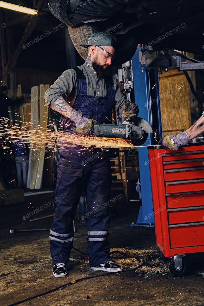 Mechaniker schneidet Stahl Autoteil mit einem Winkelschleifer.