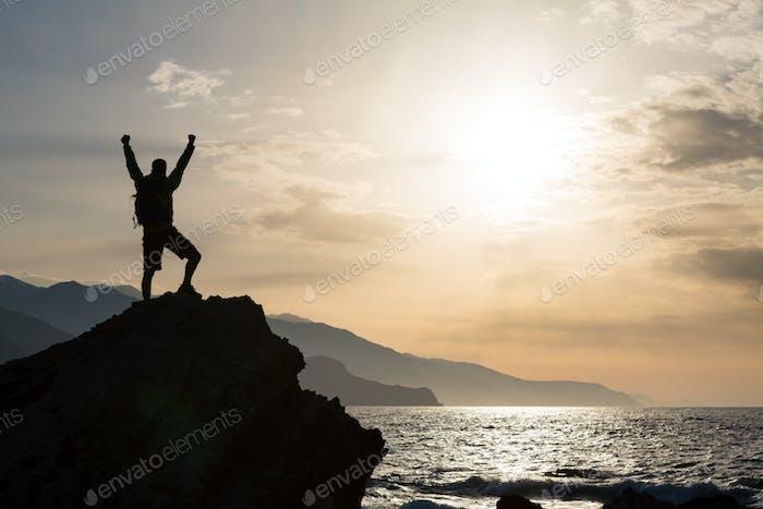 Mann mit ausgestreckten Armen feiern Berge Sonnenaufgang