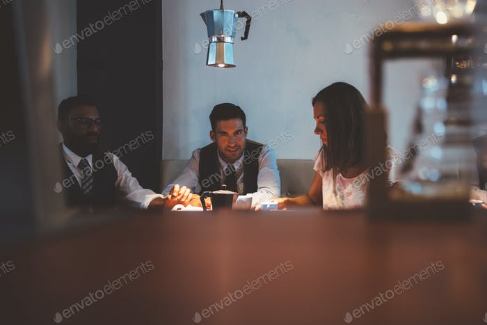 Three people at table with coffee maker above