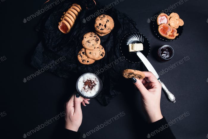 Woman hand with cup of coffee or cappuccino and chocolate cookies