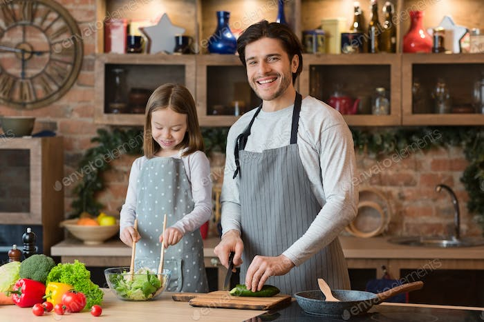 Happy father and daughter cooking breakfast together in kitchen, enjoying organic food