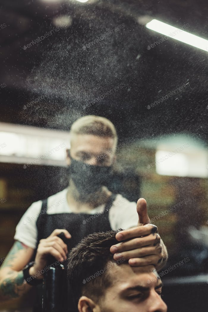Stylist grooming client in barbershop