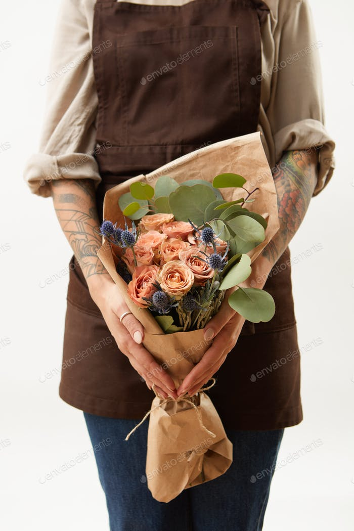 Woman in a brown apron is holding summer wonderful fresh roses, eryngium and green leaves as a