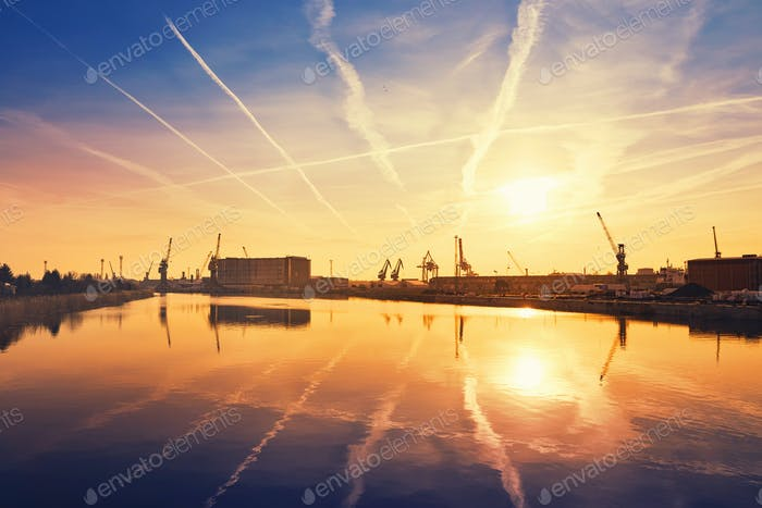 Sunrise over crane silhouettes in Szczecin harbor, Poland.