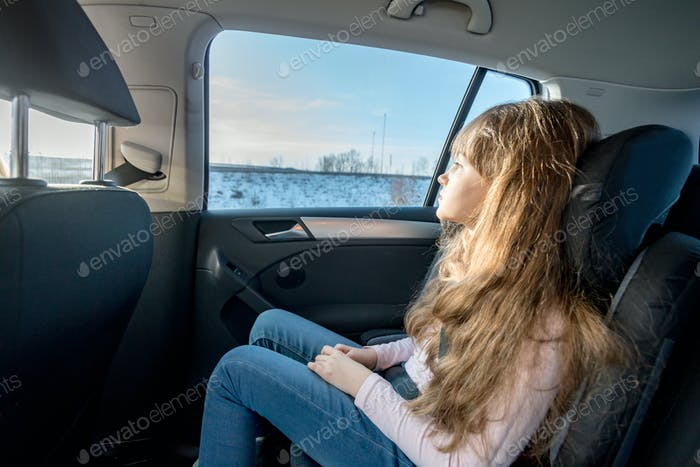 Boring little girl sitting in car seat and looking through window during long journey