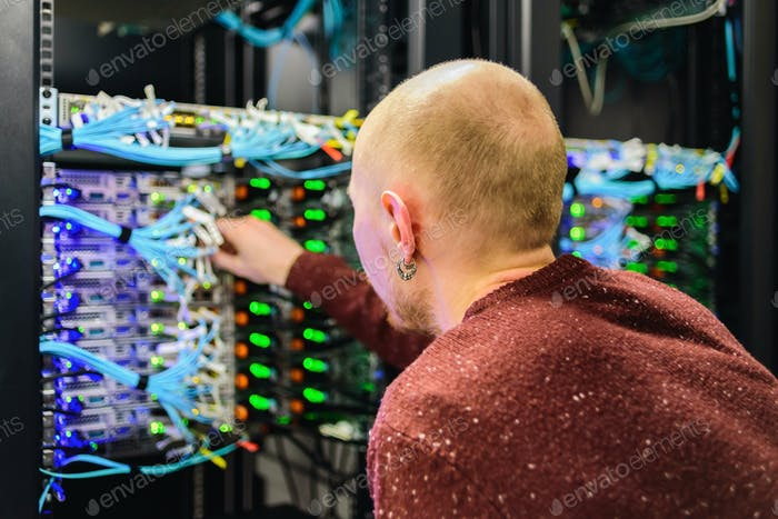 Man data center technician performing server maintenance